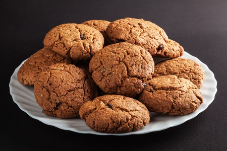 White plate of freshly baked oatmeal cookies with chocolate Stock Photo