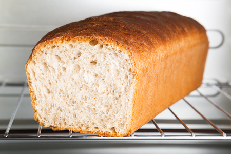 A loaf of delicious freshly baked wheat bread is on the grill