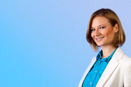 Studio portrait of a young beautiful businesswoman in a blue shirt and beige jacket Stock Photo