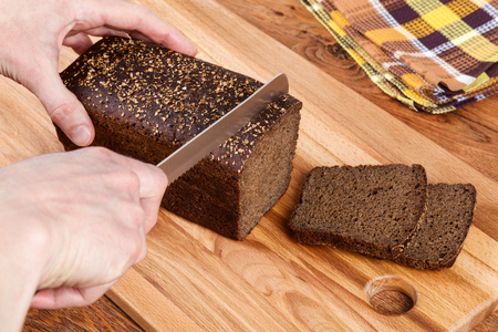 carbohydrates: Cutting delicious homemade black bread. Borodinsky bread is a traditional Russian rye-wheat bread with maltose syrup, malt and coriander