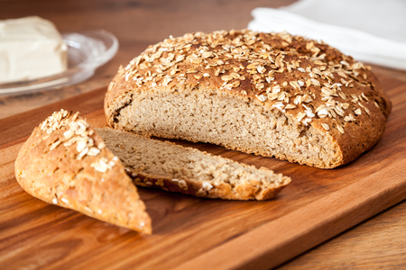 sprinkled: Delicious wheat-rye sourdough bread. Homemade whole grain bread sprinkled with oat flakes closeup