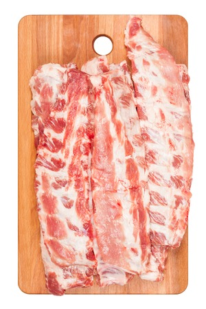 Raw pork ribs on wooden cutting Board closeup. White background, top view Stock Photo