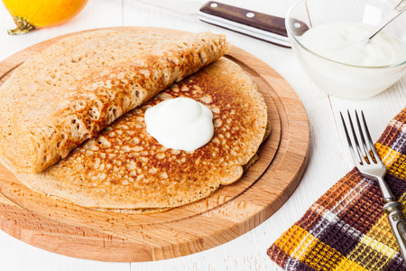 Traditional Russian blini with sour cream close-up. Homemade yeast pancakes with healthy wholegrain flour