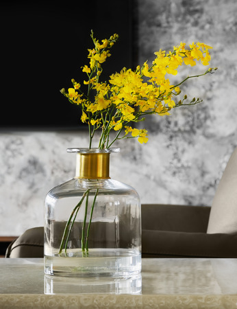 Home interior decor. Bouquet of yellow flowers  in a vase on table, on a grey wall background. Stock fotó