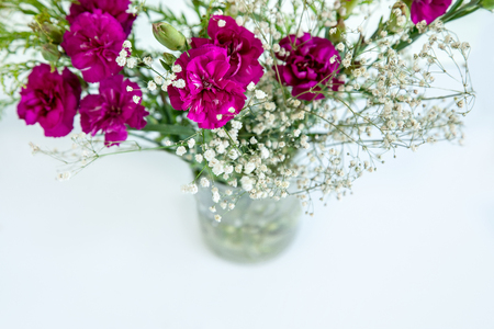 White little flowers and fuchsia flowers on white background.