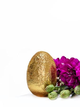 Golden egg and blossom fuchsia flowers on white background. 版權商用圖片