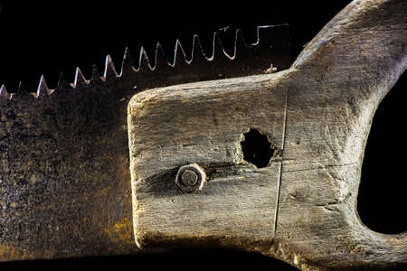 serrucho: Old handsaw on the black background - closeup