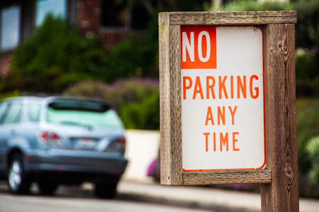 parking violation: No Parking Anytime - Sign made of wood with car on the background Stock Photo