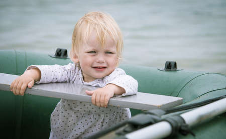 Portrait of a baby sitting in the old row boat Standard-Bild - 105020514