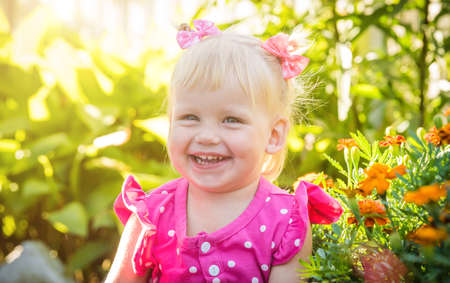 Beautiful happy little baby girl on a green bright summer background