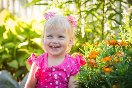 Beautiful happy little baby girl on a green bright summer background Standard-Bild - 107027701