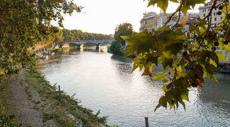 Beautiful ancient bridge over the calm river in the central part of Rome Standard-Bild - 115453579