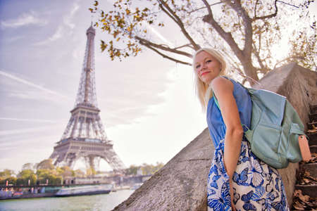 Blond girl looking at the Eiffel tower in Paris
