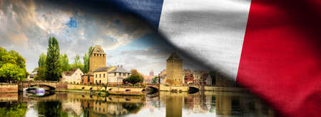 Fabric Flag of france and Strasbourg cityscape, Alsace, France. Traditional half timbered houses of Petite France. Standard-Bild - 118619711