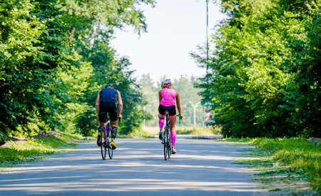 jumpsuit: Beautiful young pair of professional cyclists riding on the road surrounded by green trees on a bright and sunny day. Girl in pink jumpsuit with a helmet, guy in a dark blue special suit.