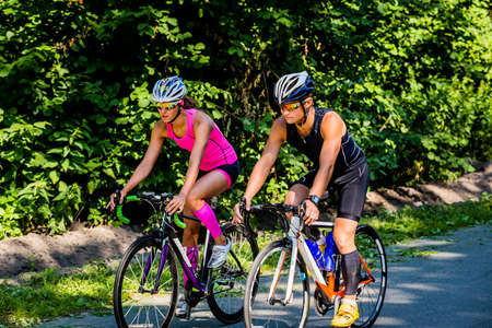 jumpsuit: Beautiful young pair of professional cyclists in gear and glasses riding on the road surrounded by green trees on bright sunny day. Girl in pink jumpsuit with helmet, guy in dark blue special suit.