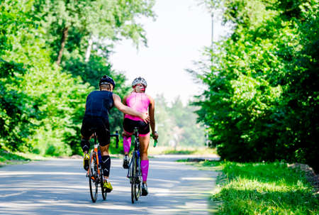 Beautiful young pair of professional cyclists riding on the road cose to each other hugs surrounded by green trees on a bright and sunny day.Girl in pink jumpsuit with a helmet,guy in a dark blue suit