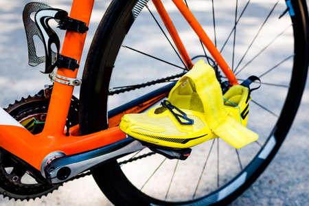 ciclismo: Primer plano de la rueda trasera negro de la bicicleta, un cuadro naranja, amarillo brillante zapato de ciclismo en el primer plano listo para iniciar las competiciones de la etapa de ciclismo en un triatlón. Foto de archivo