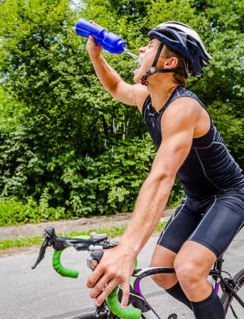 triathlon: Professional cyclist wearing a helmet and a black suit triathlon drinking water from blue plastic jar on the move in competition