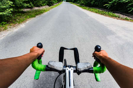 asphalting: Riding on flat road asphalting in the forest. Hands on the steering wheel bicycle. Eye view from cyclist head