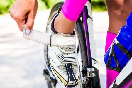 shoes: Professional cyclist triathlete buttons cycling shoes on the clasp to secure the foot on the pedal bike.