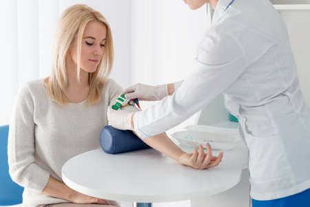 白衣医療制服白の明るい部屋でテーブルの上の女性医師が若い金髪美人と血液検査のための準備。看護師患者の手はグリップ緑のジュートです。