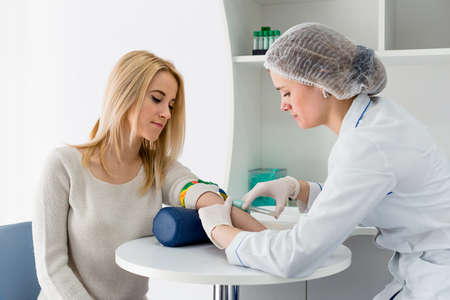 Blood test from vein with beautiful young blond woman by female doctor in white coat medical uniform on the table in white bright room.