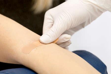 白い手袋で看護師は、静脈から採血の手順の最後で患者の腕にパッチを貼り付けます。