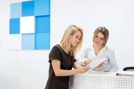 consulting: Medical worker consults patient in the central bright and white hall of the hospital. Patient beautiful young blond woman standing near the reception and holding a brochure. Stock Photo