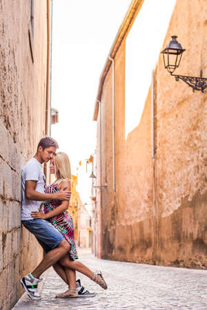 spainish: Beautiful couple hugging in narrow spainish street in shadow from big wall Stock Photo