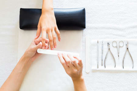 nail scissors: Woman having a manicure in a beauty salon with the beautician filing her nails with a file, over head view of the hands Stock Photo