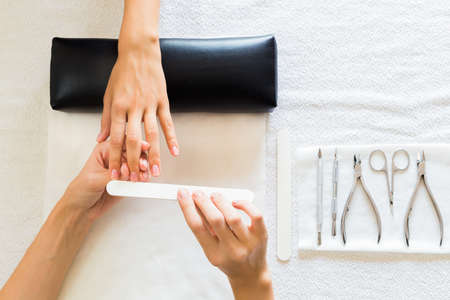 nail scissors: Beautician performing a manicure in a salon on a lady client filing her nails with a file, view from above of their hands and tools