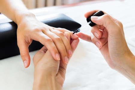 manicura: Manicuro que pone el suavizante de la cutícula de las uñas de las manos de un cliente dama en un salón de belleza con un pequeño aplicador