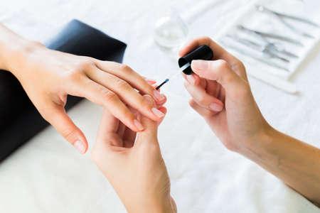 manicura: Manicurista aplicar suavizante de la cutícula o barniz de uñas transparente para las uñas de las manos de un cliente dama en un salón del balneario o de la belleza, de cerca de las manos