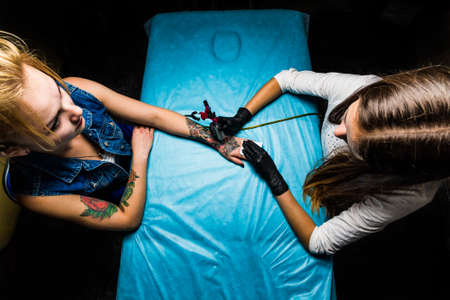 cover girls: Top view master tattooist makes the tattoo on the blond girls hand. Girls in salon and work on blue table cover. Master works in professional sterile black gloves and pink tattoo machine.