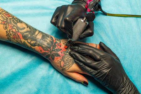artistas: Close up artista del tatuaje dibujo pintura naranja en un tatuaje negro y rojo en la mano los clientes en una estera profesional azul. Maestro tatuaje celebrar una máquina de tatuaje y en negro guantes estériles.