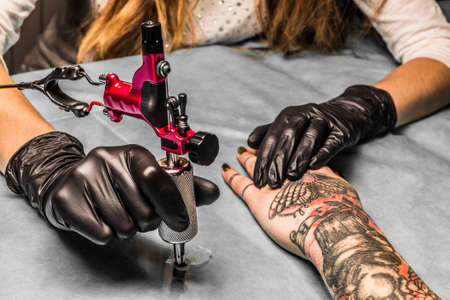 butterfly in hand: Tattoo artist takes an orange paint for black and red tattoo which draws for a girl. Master works in a professional salon with pink tattoo machine on a blue mat and in sterile  black gloves.