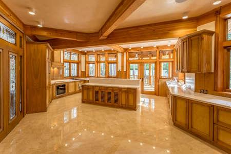 エコハウスで木製の大きなキッチン。キッチンの家具と大理石の上部と床。キッチンの窓は、緑豊かな庭園を表示します。新しい、現代設備を設計