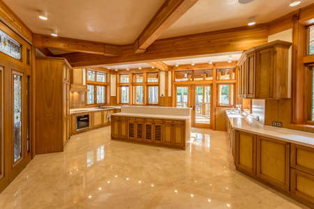 Large kitchen made of wood in eco house. Kitchen furniture and marble top and floor. The windows in the kitchen views the green garden. Design facilities new and modern.