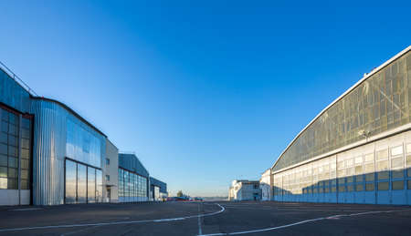 The area between aircraft hangars. Buildings are large and gray on the road with aviation markings. The weather is sunny with blue clear sky.
