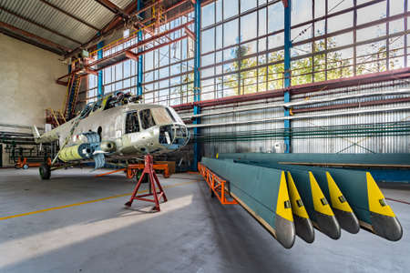blades: Helicopter without blades in repair stand in the aviation hangar. Helicopter blades stand nearby.