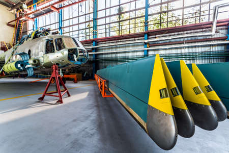 Helicopter rotor blades removed from aircraft. Air transport stand in the aviation hangar. Stock Photo