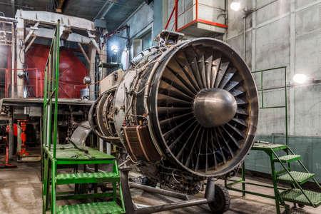 Airplane gas turbine engine detail in aviation hangar. Plane rotor under heavy maintenance.