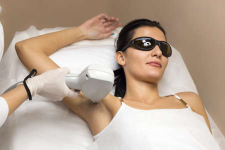 Brunet woman having underarm Laser hair removal epilation. Laser treatment in cosmetic salon. Cosmetologist in white sterile gloves.