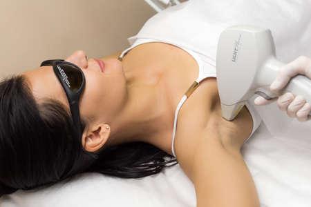 depilacion: La depilación láser en el estudio profesional de la belleza. Esteticista en guantes estériles blancos hacer el procedimiento en la axila del cliente.