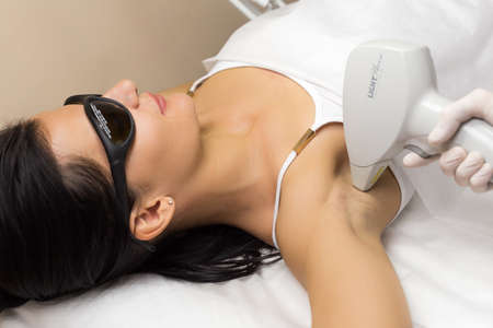 Laser hair removal in professional beauty studio. Beautician in white sterile gloves make the procedure on the clients armpit. Stock Photo
