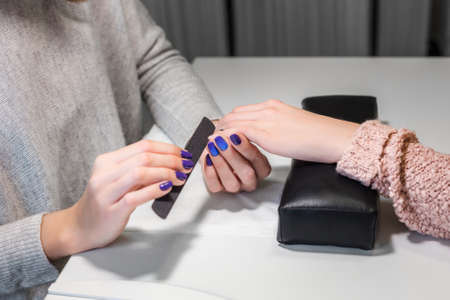 emery: Processing nails with emery nail-file in beauty nail salon.Client receiving manicure by beautician. Gentle care of nails in cosmetic salon. Nail file. Manicure process. Stock Photo