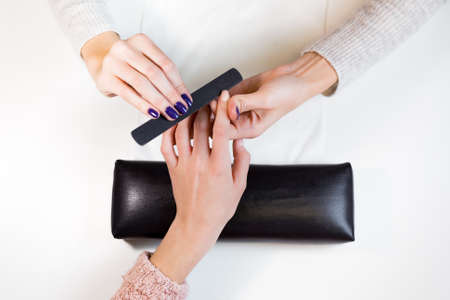 manicurist: Top view manicurist polishing index finger for manicure in nail beauty salon. Step of manicure process.