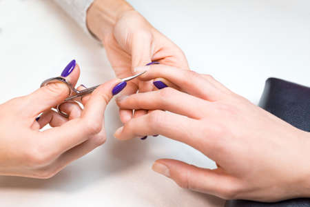 nailpolish: Top view closeup beautician works with nail scissors client ring finger on pure white table with professional tools for manicure and pedicure.