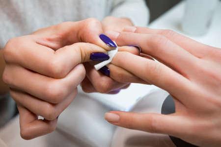 ハンドル滅菌ホワイト コットン布クライアントを女の子には、ニスの爪をペイントしたり、スパのサロンでシェラック爪をマニキュアします。ネイ 写真素材